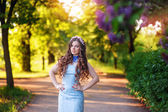 Beautiful young woman in the garden of lilacs in the spring — Stock Photo