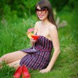 Happy young woman in sunglasses sitting on the grass with a cock — Stock Photo #65304445