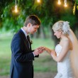 Groom wears the ring bride under the arch — Stock Photo #65391537
