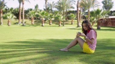 Beautiful woman sitting on grass in summer city park with phone — Stock Video