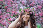 Young woman in a park with a spring wreath — Stock Photo