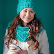 Young woman in knit scarf and hat listening to music on headphon — Stock Photo #65797111