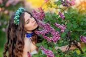 Happy young woman smelling a spring branch of lilac flowers — Stock Photo