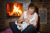 Happy mother bottle fed baby girl by the fireplace — Stock Photo