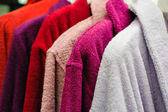 Colored terry bathrobes hanging on the store trempel — Stock Photo