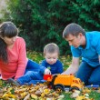 Young family with a child walks in autumn park — Stock Photo #68607585