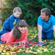 Young family with a child walks in autumn park — Stock Photo #68613801