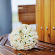 Beautiful wedding bouquet of white roses lying on a bench — Stock Photo #68843339