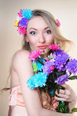 Beautiful girl in the studio with a bunch of flowers — Stock Photo