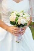 Bride holding a beautiful white wedding bouquet — Stock Photo