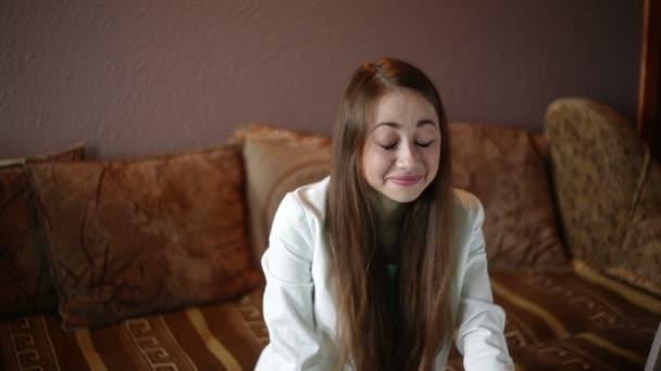Hermosa mujer sentada en el sofá y viendo la televisión — Vídeo de stock