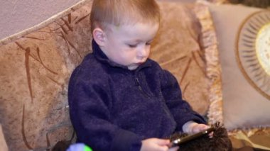 Little boy sitting on the couch and watching a cartoon on your smartphone — Vídeo stock