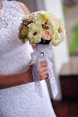 Bride holding a beautiful wedding bouquet — Stock Photo