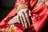 Hands of a bride in a red robe with a wedding ring on her finger — Stock Photo