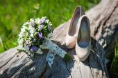 Beautiful wedding bouquet and shoes for the bride standing on a — Stock Photo