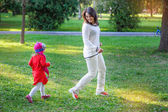 Mom and little daughter walking in the summer park — Stock Photo