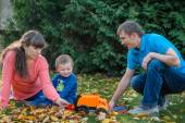 Young family walking in autumn garden — Photo