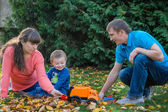 Young family walking in autumn garden — Stock Photo