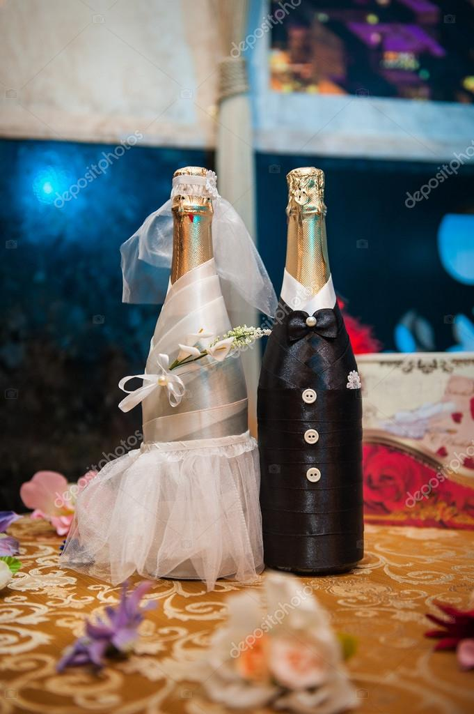 Two bottles of champagne decorated as a bride and groom standing - Imagem Stock: 71724851