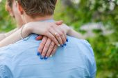 Bride embraces bridegroom's neck rear view — Stock Photo