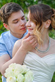 Groom kisses the bride on a background of green leaves in the sp — Stock Photo