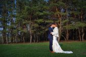 Groom kisses the bride on a background of pine forest in the spr — Stock Photo