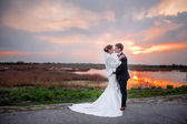 Bride and groom near the lake in the evening at sunset — Stock Photo