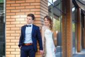 Bride and groom are standing on the corner of the house and hold — Stock Photo