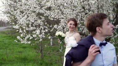 Bride and groom are in the blossoming spring garden — 图库视频影像