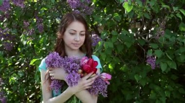 Beautiful woman walking in spring park with a bouquet of lilac — Stock Video