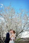 Beautiful newlyweds walking in spring blooming garden — Stock fotografie
