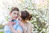 Bride embraces bridegroom in the blossoming spring garden — Stock fotografie