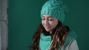 Beautiful girl in a knitted hat listening to music on headphones — Stock Video