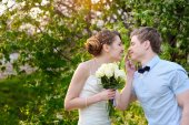 Bride and groom walking in the blossoming spring garden — Stock Photo