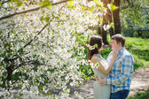 Beautiful newlyweds walking in spring blooming garden — Stock Photo