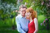Young couple in love walking at the blossoming spring garden — Stock Photo