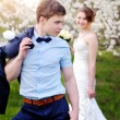 Bride and groom walking in the blossoming spring garden — Stock Photo #75822403