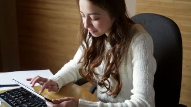 Beautiful young woman in a white sweater working at a computer — Stock Video