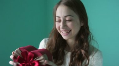 Beautiful young smiling woman with a gift in the form of heart in her hands — Vidéo