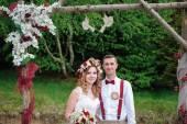 Bride and groom near wedding arch — Stock Photo