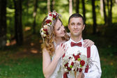 Happy bride and groom walking in the summer forest — Stock Photo