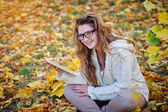 Young woman with a tablet sitting in the autumn park — Stock Photo
