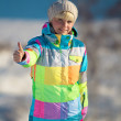 Girl in a ski suit standing with outstretched hand and shows thumb — Stock Photo #63626279