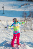 Girl in a ski suit standing stretched in different directions hands and eyes closed — Stock Photo