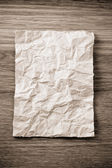 Wrinkled paper  on wood — Stock Photo