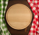 Cutting board on wooden background — Stock Photo