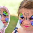 Little girl getting her face painted — Stock Photo #56128807