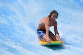 Man ride a surfing board on FlowRider — Stock Photo