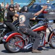 Постер, плакат: Men ride Harley Davidson motorcycle in city street