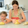 Mother and child kneading dough — Stock Photo #60801005